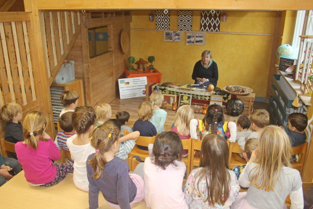 """Die Kinder der städtischen Kindertagesstätte verfolgen fasziniert in der liebevoll eingerichteten """"afrikanischen Ecke"""" die Märchenlesung von Anne Hagel"""